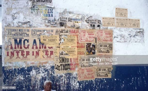 Visage d'une femme appuyée contre un mur recouvert d'affiche en septembre 1982 Mexique