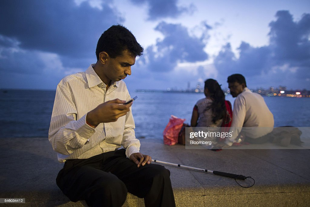 Vishal Agrawal, a foreign exchange trader at Standard Chartered Plc, listens to foreign exchange rates using his mobile phone while sitting on the waterfront at Nariman Point in Mumbai, India, on Thursday, June 9, 2016. Agrawal was diagnosed with the degenerative eye disease retinitis pigmentosa in 2004 as he was preparing to leave for under graduate study in U.S. Constrained by the diagnosis, he settled for studying accounting close to his home in Mumbai. Photographer: Prashanth Vishwanathan/Bloomberg via Getty Images