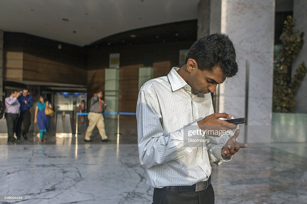 Vishal Agrawal, a foreign exchange trader at Standard Chartered Plc, books an Uber Technologies Inc. taxi using his mobile phone in Mumbai, India, on Thursday, June 9, 2016. Agrawal was diagnosed with the degenerative eye disease retinitis pigmentosa in 2004 as he was preparing to leave for under graduate study in U.S. Constrained by the diagnosis, he settled for studying accounting close to his home in Mumbai. Photographer: Prashanth Vishwanathan/Bloomberg via Getty Images