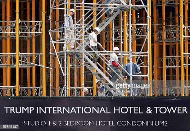Visible beyond a promotional banner workers move down construction stairs as construction continues on the Trump International Hotel Tower a new...