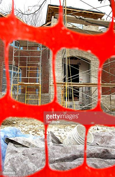 Visible through a safety fence, scaffolding is seen on a new home is under construction November 20, 2002 in Park Ridge, Illinois. In a report...