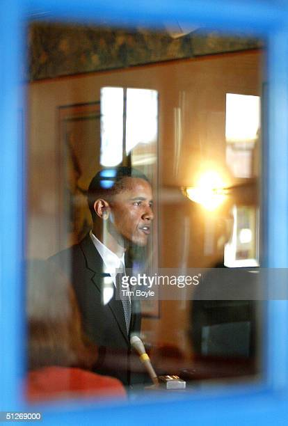 Visible through a window pane US Senate candidate Barack Obama speaks to the media at the Ann Sather restaurant September 7 2004 in Chicago Illinois...