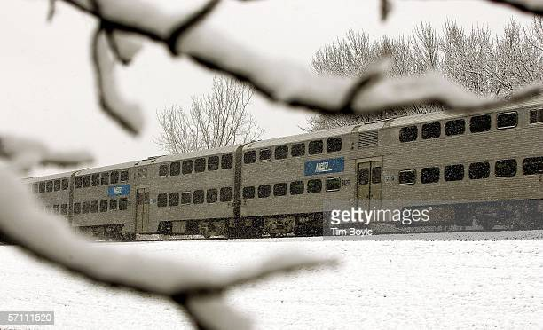 Visible through snowy tree branches a lateafternoon Metra commuter train makes it way along the tracks March 16 2006 in Des Plaines Illinois With...