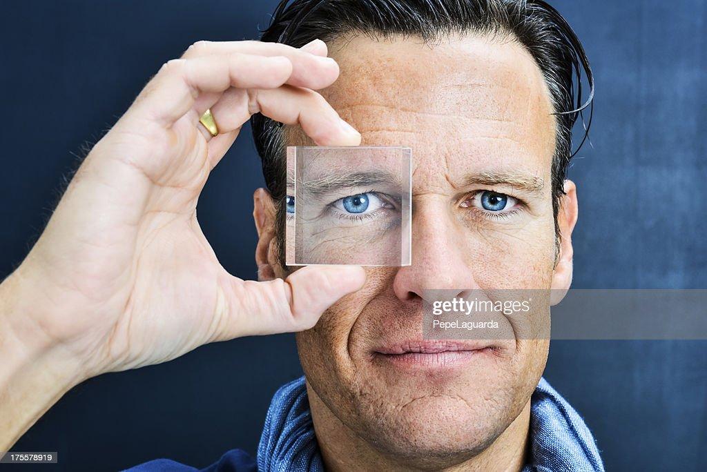 Vision: man looking through lens : Stock Photo
