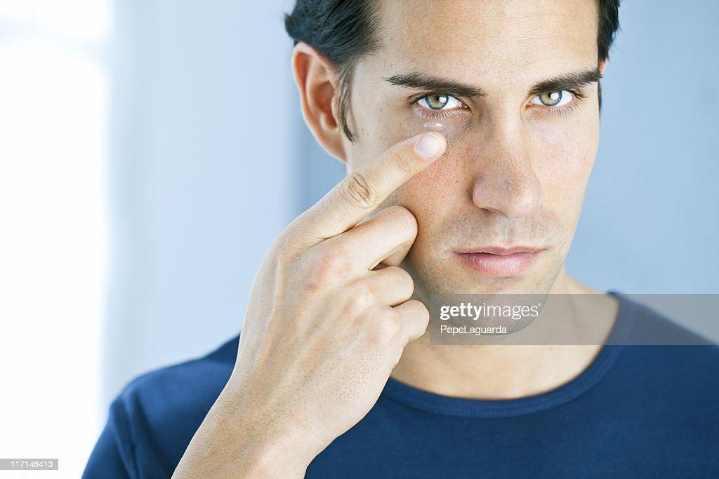 Vision: man using a contact lens : Stock Photo