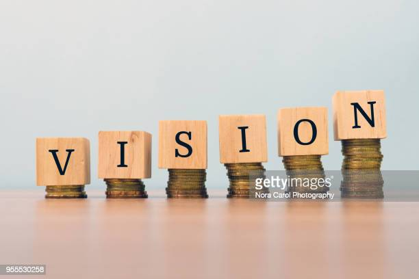 Vision text written on wooden block with stacked coins