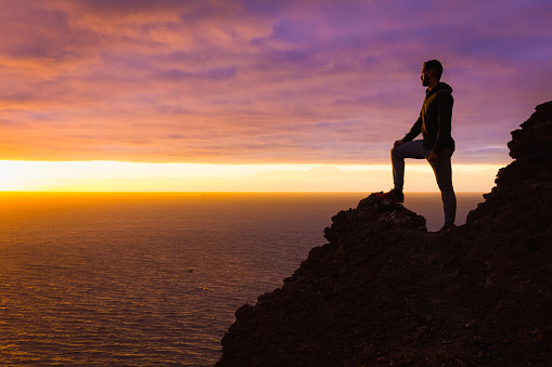 Visionary man standing on top of cliff edge staring at colorful sunset by the sea in Gran Canaria 1126007754
