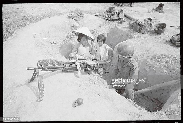 Visit with DaddyA South Vietnamese soldier is visited by his wife and children March 21 while he is on guard duty in trench along Highway 13 some 20...