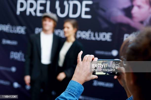 A visiter takes a photo of Liv Lisa Fries and Louis Hofmann by using a smartphone during the Prelude film premiere at Filmtheater am Friedrichshain...