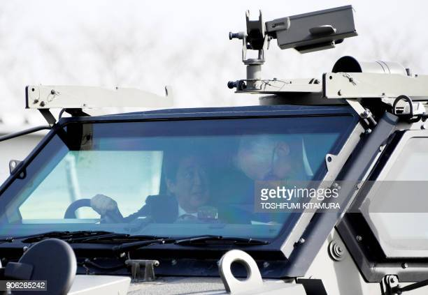 Visiting Australian Prime Minister Malcolm Turnbull and Japanese Prime Minister Shinzo Abe sit on the driving and front seats of an Australianmade...