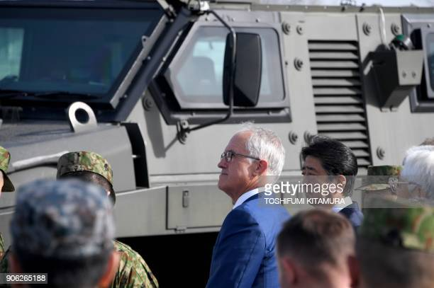 Visiting Australian Prime Minister Malcolm Turnbull listens to a military chief with Japanese Prime Minister Shinzo Abe beside an Australianmade...