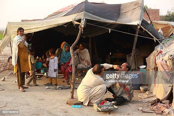 CONTENT] A visiting barber making shave of the Slum's owner in front of his family while they are enjoying how a photographer trying to capture him