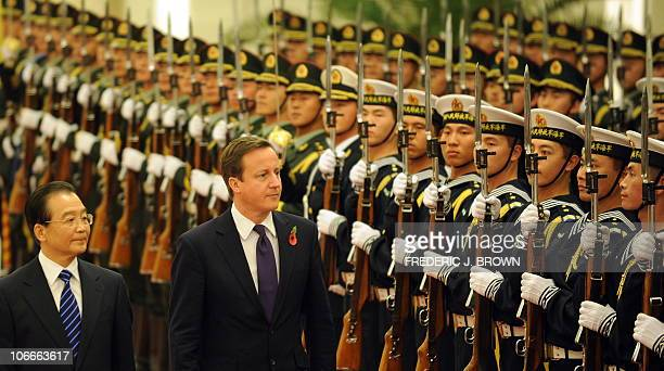 Visiting British Prime Minister David Cameron walks beside Chinese Premier Wen Jiabao while wearing a poppy on his lapel to honor British war dead at...