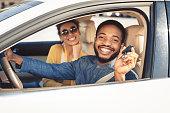 Visiting car dealership. Afro couple showing car key