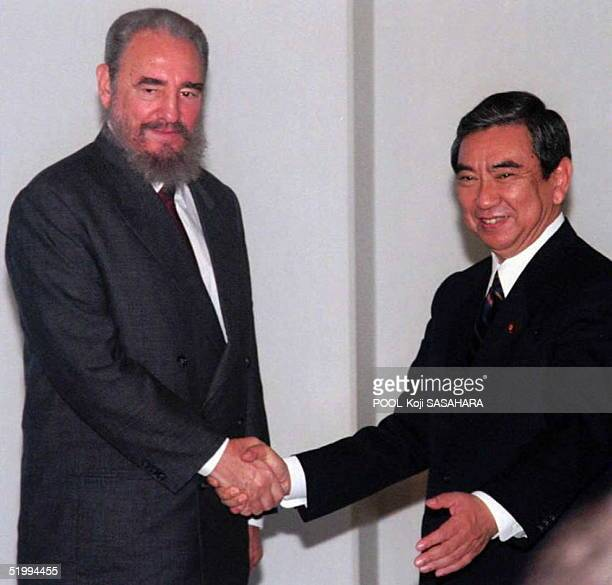 Visiting Cuban President Fidel Castro and Japanese Foreign Minister Yohei Kono shake hand prior to their meeting at a hotel in Tokyo 13 December...