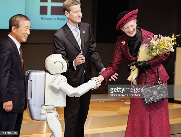 Visiting Danish Queen Margrethe II shakes hands with Honda Motor's humanoid robot Asimo after he offers a flower bouquet at the Honda headquarters in...