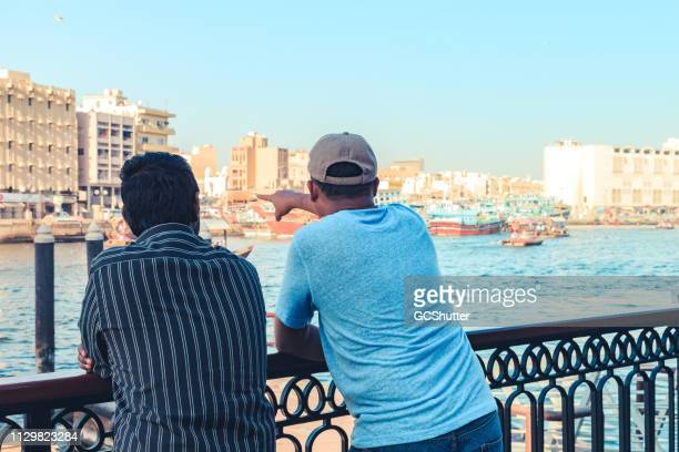 visiting dubai creek and admiring the old dubai - tourboat stock pictures, royalty-free photos & images