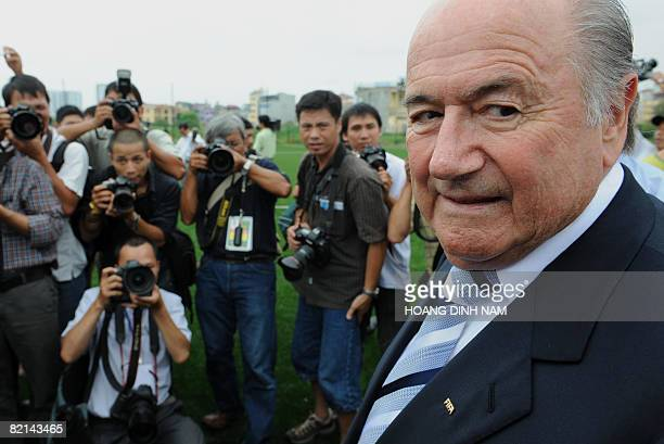 Visiting FIFA president Sepp Blatter poses for photographers as he attends the opening of a newly laid football pitch in Hanoi on August 1 which was...