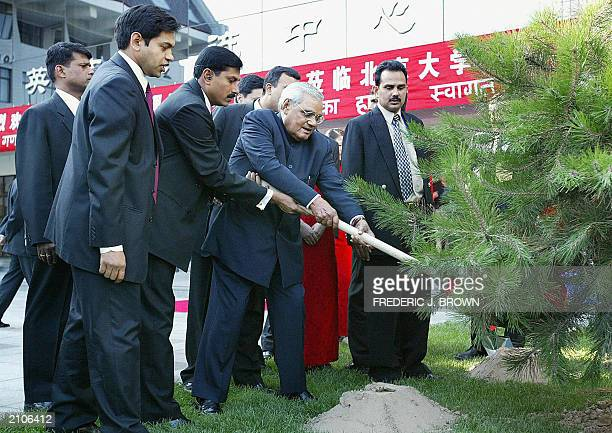 Visiting Indian Prime Minister Atal Behari Vajpayee is assisted as he shovels dirt for a treeplanting ceremony at the Peking University Exchange...