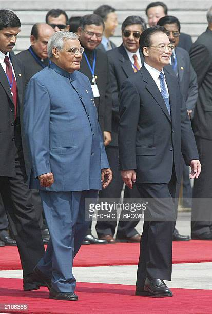 Visiting Indian Prime Minister Atal Behari Vajpayee walks beside Chinese Premier Wen Jiabao during a welcoming ceremony 23 June 2003 at the Great...