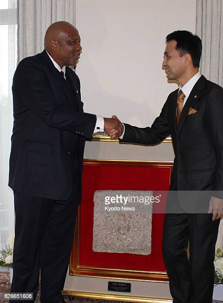 Visiting Lesotho King Letsie III shakes hands with Michio Umemoto, principal of the Stone for Peace Association of Hiroshima, as he receives a peace...