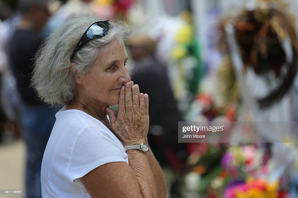 Visiting member of the Order of St. Luke Susan Keefe stands in front of the Emanuel AME Church on the one-month anniversary of the mass shooting on July 17, 2015 in Charleston, South Carolina. Visitors from around the nation continue to pay their respects at a makeshift shrine in front of the church, in a show of faith and solidarity with 'Mother Emanuel', as the church is known in Charleston. Nine people were allegedly murdered on June 17 by 21-year-old white supremacist Dylann Roof, who was captured by police in North Carolina the following day. He is scheduled to go to trial July 11, 2016.