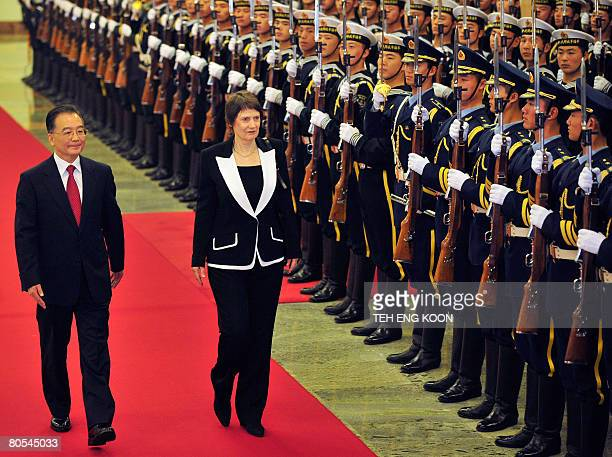 Visiting New Zealand Prime Minister Helen Clark walks with her Chinese counterpart Wen Jiabao as they inspect the guard of honor during a welcoming...