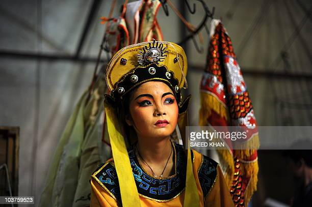 A visiting performer from mainland China waits backstage to take part in a Chinese opera during a Hungry Ghost festival in Malaysia's northern town...