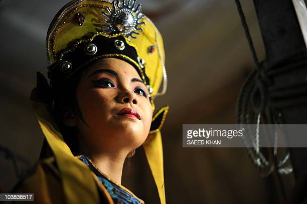 """Visiting performer from mainland China waits backstage to take part in a Chinese opera during a """"Hungry Ghost"""" festival in Malaysia's northern town..."""