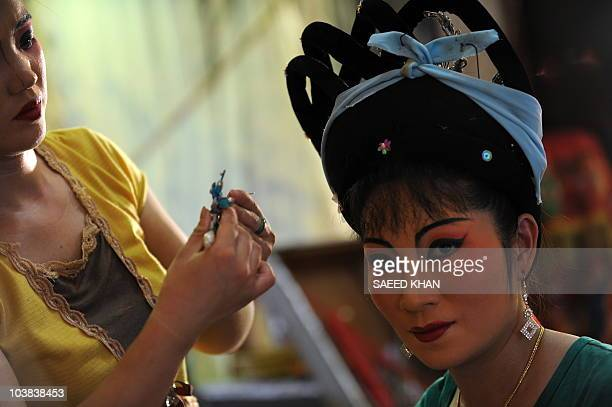 "Visiting performers from mainland China apply makeup in preparation for a Chinese opera during a ""Hungry Ghost"" festival in Malaysia's northern town..."