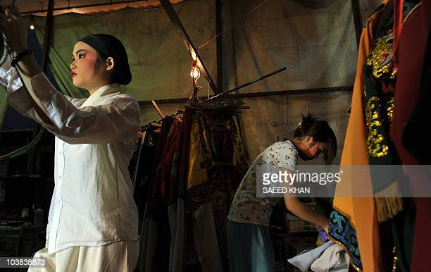 Visiting performers from mainland China stand backstage as they prepare to take part in a Chinese opera during a Hungry Ghost festival in Malaysia's...