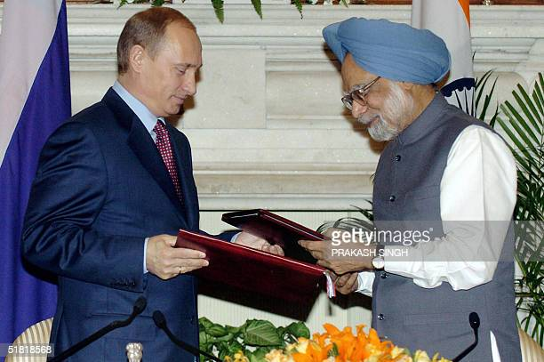 Visiting Russian President Vladimir Putin and Indian Prime Minister Manmohan Singh exchange documents after they signed an agreement 03 December 2004...