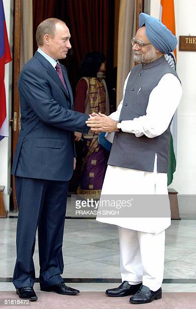 Visiting Russian President Vladimir Putin shakes hands with Indian Prime Minister Manmohan Singh 03 December 2004 in New Delhi prior to a meeting...