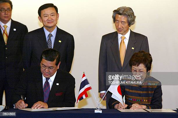 Visiting Thai Foreign Minister Surakiart Sathirathai and his Japanese counterpart Yoriko Kawaguchi sign documents as Thai Prime Minister Thaksin...