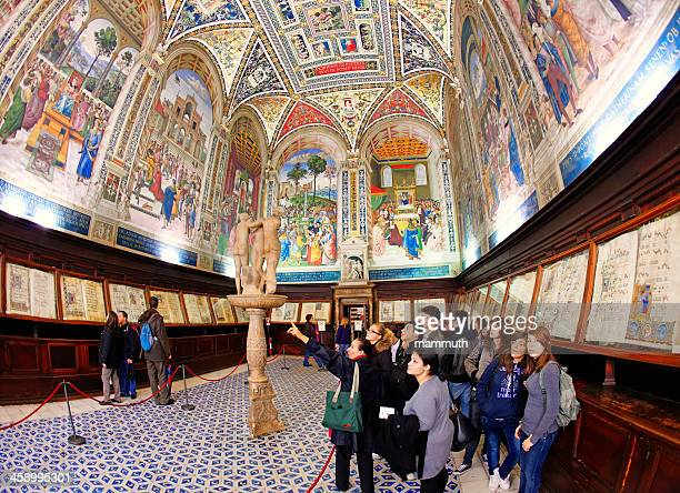visiting the piccolomini library in siena cathedral - siena italy stock pictures, royalty-free photos & images