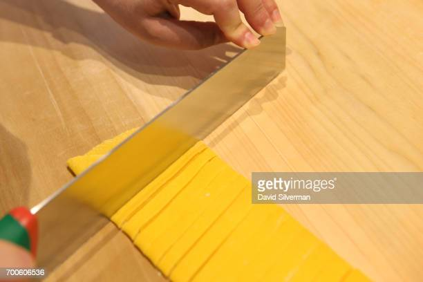 Visiting tourist Nava Goldstein cuts fettuccine from handmade pasta during a private cooking lesson at Il Salotto di Penelope on March 30 2017 in...