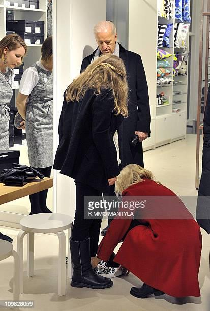 US Visiting Vice President Joe Biden looks at his granddaughter Finnegan and his wife Jill at a Marimekko store in Helsinki on March 7 2011 Finnegan...