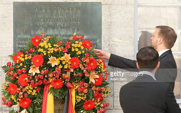 A visitor adjusts flowers on a plaque dedicated to the memory of the planners of the 1944 assassination attempt on Adolf Hitler on the 69th...