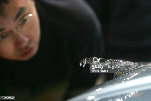 A visitor admires a Jaguar sedan at the 2006 International Automotive Exhibition November 19 2006 in Beijing China The week long exhibition showcases...