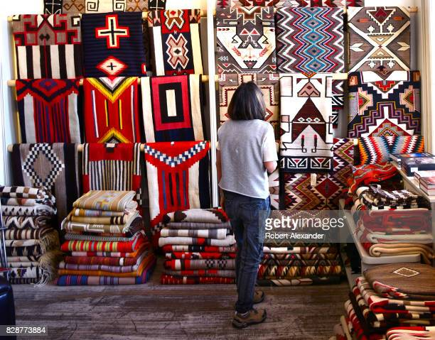 A visitor admires Native American rugs made by weavers from the Navajo Nation for sale in a shop in Santa Fe New Mexico