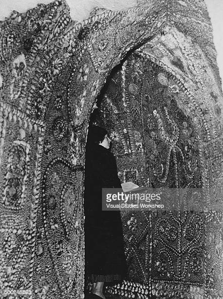 A visitor admires one of the walls of the Shell Grotto an underground temple decorated entirely with seashells in mosaic patterns and flowers and...