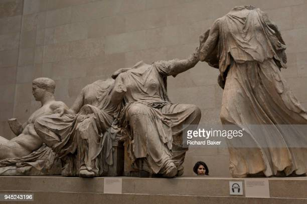 A visitor admires the sculpture of the ancient Greek Parthenon's Elgin Marbles Metopes in the British Museum on 11th April 2018 in London England