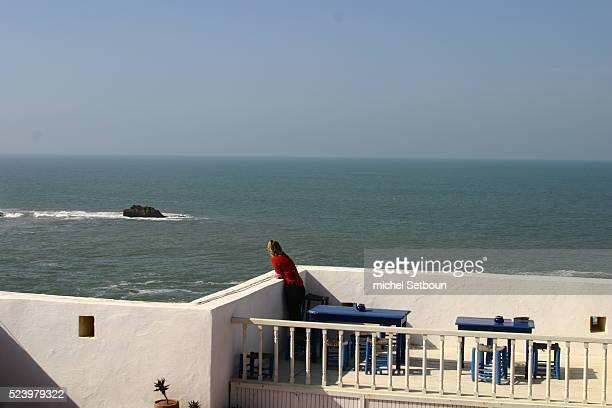 A visitor admires the view from the terrace of the Hotel des Artistes which overlooks Essaouira's famous ramparts