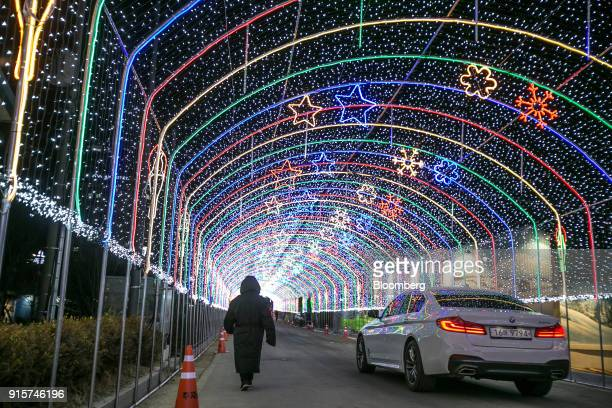 A visitor and a Bayerische Motoren Werke AG automobile pass under LED light decorations ahead of the 2018 PyeongChang Winter Olympic Games in the...