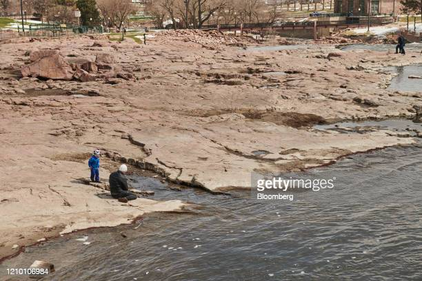 A visitor and child are seen at Falls Park in Sioux Falls South Dakota US on Wednesday April 15 2020 South Dakota Governor Kristi Noem has argued...