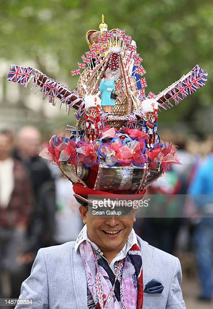 A visitor arrives wearing a hat decorated with a crown British flags dolls and an effigy of Queen Elizabeth II at St James Park prior to the Diamond...