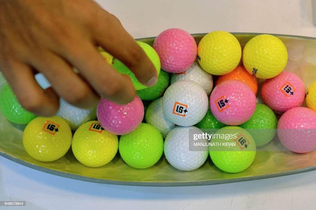 A Visitor At A Stall Looks At Colourful Indian Made Golf Balls On Display During