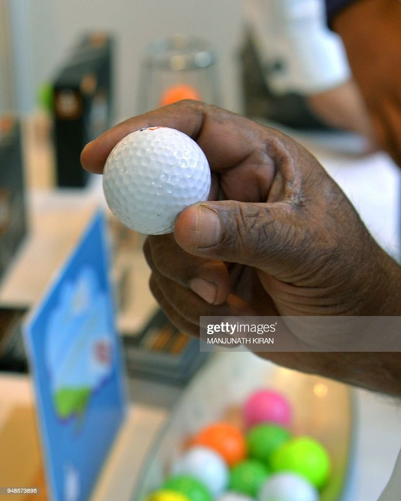 A Visitor At A Stall Looks At Indian Made Golf Balls On Display During The