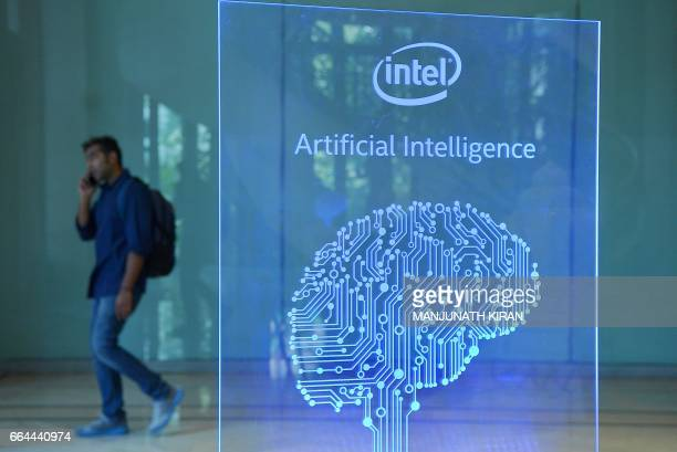 A visitor at Intel's Artificial Intelligence Day walks past a signboard during the event in the Indian city of Bangalore on April 4 2017 / AFP PHOTO...