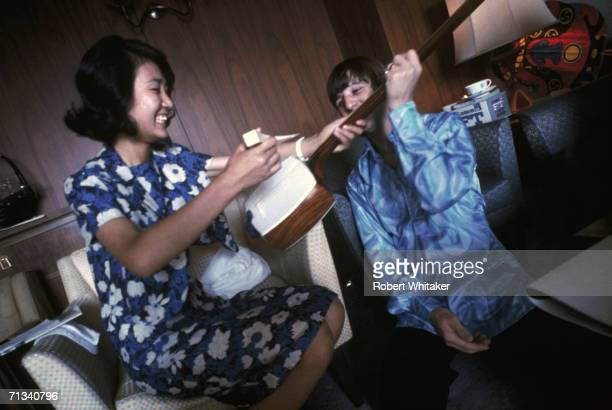 A visitor at the Beatles suite at the Tokyo Hilton presents Ringo Starr with an ornate Japanese stringed instrument during the band's tour of Asia...